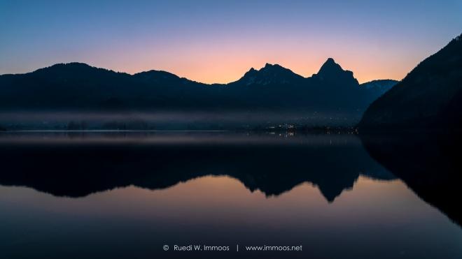 Lauerzersee vor Sonnenaufgang Spiegelung rötlich Gegenlicht_DSC9508-Signet-web